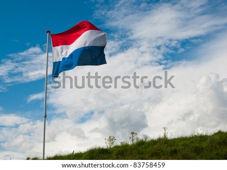 Top of a dike in the Netherlands with the Dutch national flag waving in the wind