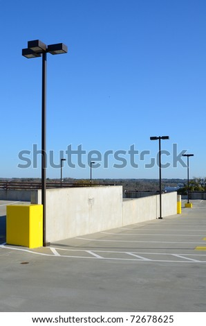 Top of a parking deck with spaces and light poles.