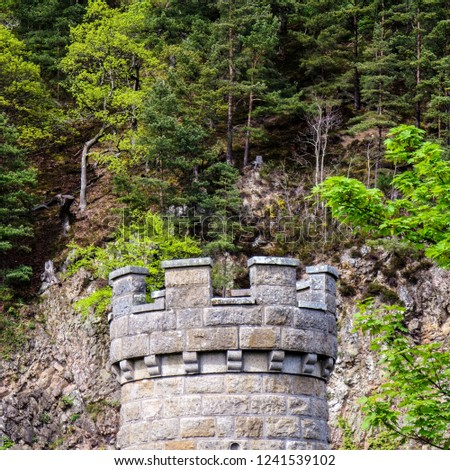 Top of ancient medieval stone tower and battlement with forest in background - Scotland