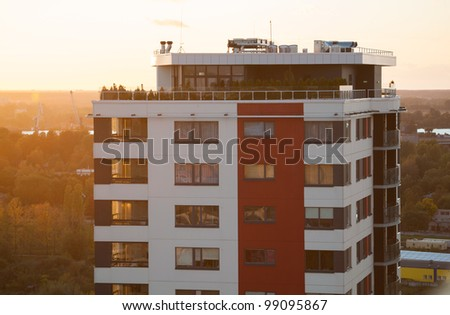 Top of modern high rise tower block in city viewed at sunset.