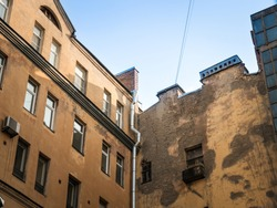 Top of old houses with drainpipe in europe city on blue sky background