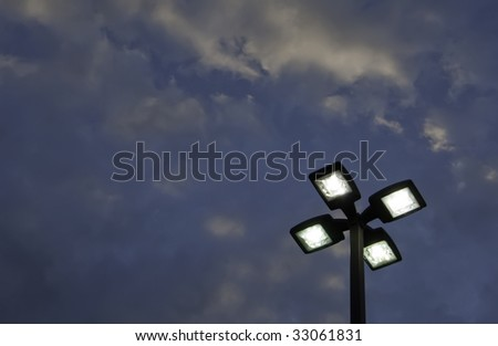 Top of outdoor lightpole with four electric lights against evening sky - stock photo