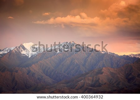 Top of snowy rock mountain on cloudy background - Shutterstock ID 400364932