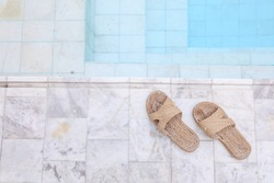 Top of weaving shoes for women on marble tile the edge of the swimming pool ,comfortable to wear for stay at home.