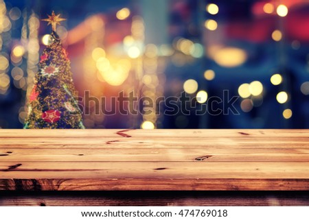 Top of wood table with christmas abstract background light bokeh from Xmas tree at night party in winter - Empty ready for your product display or montage. vintage color tone