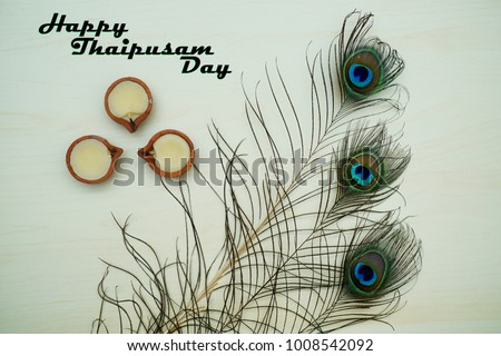 Top or flat lay view of a peacock feathers on a wooden background with a words HAPPY THAIPUSAM DAY. Celebrate by a hindu religions.  A religions conceptual. #1008542092