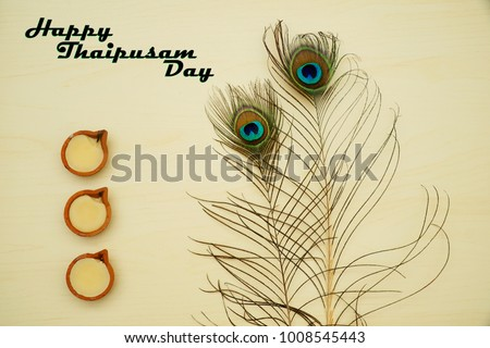 Top or flat lay view of a peacock feathers on a wooden background with a words HAPPY THAIPUSAM DAY. Celebrate by a hindu religions.  A religions conceptual. #1008545443