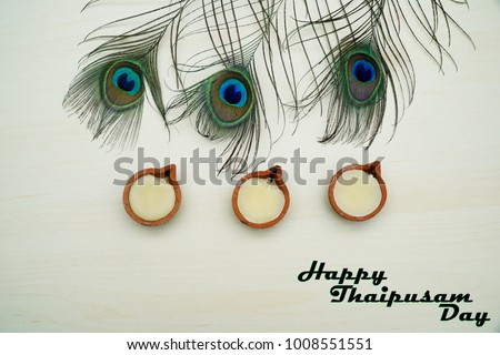 Top or flat lay view of a peacock feathers on a wooden background with a words HAPPY THAIPUSAM DAY. Celebrate by a hindu religions.  A religions conceptual. #1008551551