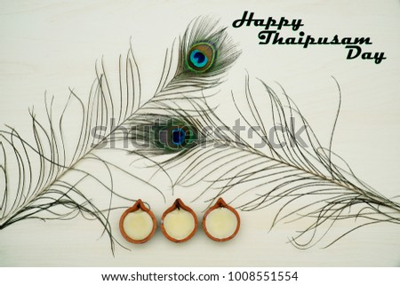 Top or flat lay view of a peacock feathers on a wooden background with a words HAPPY THAIPUSAM DAY. Celebrate by a hindu religions.  A religions conceptual. #1008551554