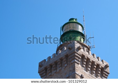 Top part of a green lighthouse made of bricks.