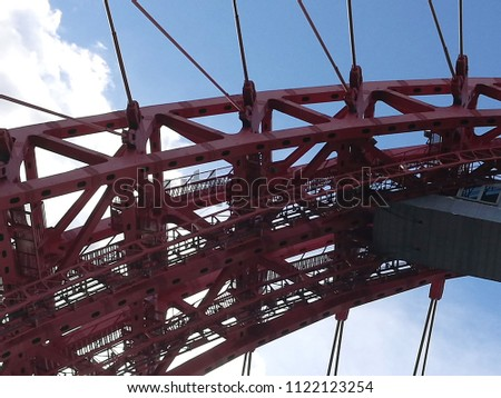 Top part of cable-stayed metal bridge against blue sky. Close-up photo of modern architecture. Urban cityscape fragment.