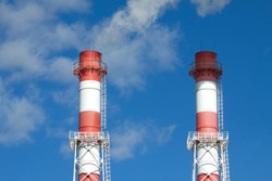Top part of two big color industrial smoke pipes over blue sky with clouds front view