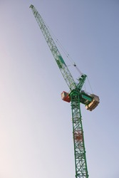Top portion a tall tower crane at sunrise with a bright sky background. Modern construction machinery with fresh green and orange colors. metal frame.