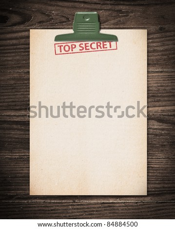 Top secret document on old wooden table.