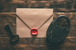 Top secret documents in envelope, rusty padlock and a key on a wooden table flat lay background. Confidential information concept.
