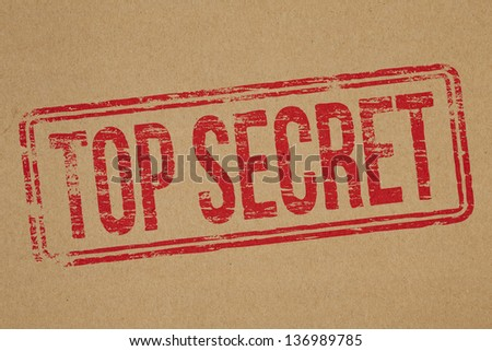 Top secret rubber stamp impression on brown paper background