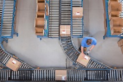 Top shot of a worker scanning boxes using a bar-code reader on conveyor belts at a distribution warehouse.