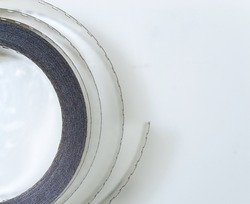 top shot of film spool on white background, rolled up 35mm cine film material.