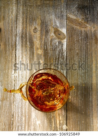 Top shot with an ice cube splashing in a glass of whiskey on a wooden background.