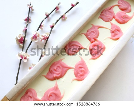 Top Surface of natural oil soap in wooden mold box, pink rose pattern on white background, cold process, handmade product.