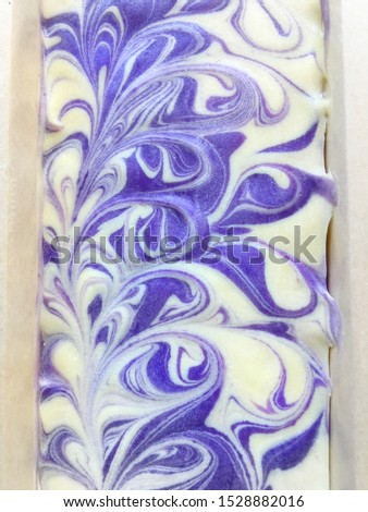 Top surface of natural oil soap in wooden mold box, purple violet and white color pattern, cold process, handmade product.