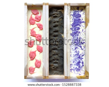 Top surface of three natural oil soap in wooden mold box, pink rose and white pattern, chocolate, purple violet, cold process, handmade product.