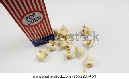 Top up high angle view above photo of single single position on table bag container with popcorn and popcorn beside isolated bright sparkle color white background