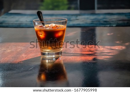 Top view a cup of Ca Phe sua da or coffee  and milk with ice on wood background. Famous traditional Vietnamese coffee in Vietnam. Milk have sugar with coffee, hot drink or with ice Foto stock ©