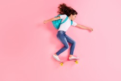 Top view above high angle flat lay flatlay lie concept full length body size view of nice cheerful cheery girl jumping standing on board riding having fun isolated on pink pastel color background