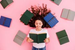 Top view above high angle flat lay flatlay lie concept portrait of her she nice lovely focused cheery wavy-haired girl reading variety different book isolated on pink pastel color background