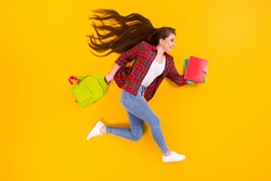 Top view above high angle flat lay lie concept of nice cheerful girl nerd running fast hurry rush late lesson course class isolated on bright vivid shine vibrant yellow color background