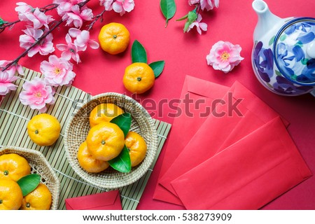 Top view accessories Chinese new year festival decorations.orange,leaf,wood basket,red packet,plum blossom,teapot on red background. #538273909