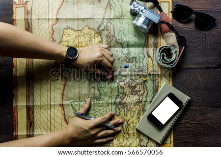 Top view accessories  travel.man planning to travel with mobile phone,camera,notepaper,map,sunglasses on table wooden with copy space.Travel concept. - Shutterstock ID 566570056