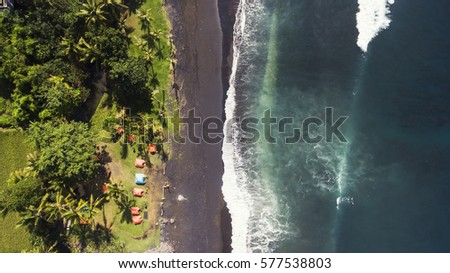 Top view aerial drone photo of black volcanic sand shore backed by thick palm trees tropical rainforest. Best camp on the beach where Indian ocean waves meet with coastline. Travel blog background