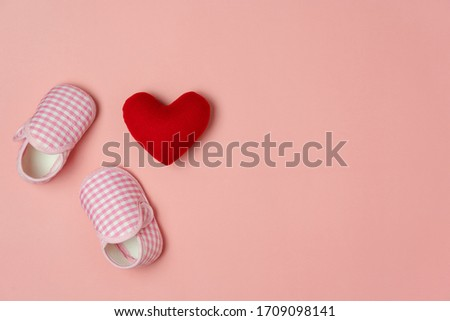 Photo of Top view aerial image of decoration Happy mothers day holiday background or women & kid fashion concept.Flat lay red love heart and baby shoes on modern pink paper.Free space for creative design text.