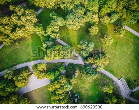 Top view aerial photo from flying drone of a city park with walking path and green zone trees in evening time