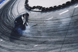 Top view aerial photo from flying drone of a professional driver drifting car on asphalt track.