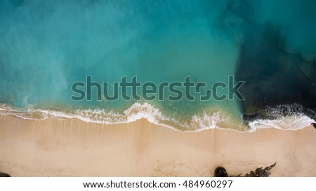 Top view aerial photo from flying drone of beauty nature landscape with paradise beach and Indian Ocean in summer day in Bali. Amazing seascape with small waves. Perfect background for travel website
