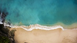 Top view aerial photo from flying drone of Indian Ocean seashore with beautiful color sea waves. Wonderful seascape with copy space for advertising text message. Perfect background for travel website