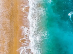 Top view aerial photo of an amazing sea waves with turquoise water from flying drone . Summer vacation holidays in Spain. Blue colours of the sea