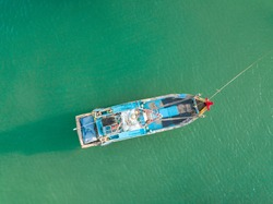 Top view, aerial view wooden fishing boat on the beach from a drone. Royalty high quality stock photo image of the wooden fishing boat on the beach. Fishing boat is mooring on clear bluw beach alone