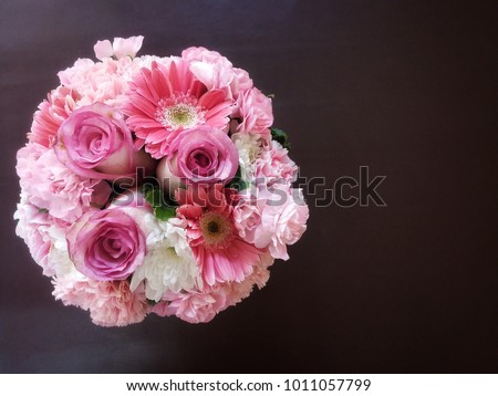 Top view and close up of pink and white flower bouquet; rose, daisy, gerbera, carnation on dark brown table background. #1011057799