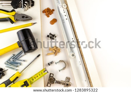 Top view arrangement group of parts for ready-to-assemble wooden furniture assembly on white board with space for copy. Equipments for diy concept.