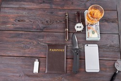 Top view arrangement of mens accessories. Passport with knife, smartphone and pen on rusitc wooden table.