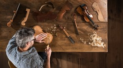Top view. Artisan luthier working on the creation of a violin. He sits at a wooden table in his workshop, various tools and instrument are placed on the workbench
