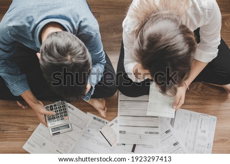 Top view asian couple sitting on the floor stressed and confused by calculate expense from invoice or bill, have no money to pay think of taking the house to mortgage causing debt, bankruptcy concept. Stockfoto ©