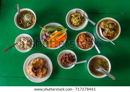 Top view at the table with assorted burmese food in local restaurant in Myanmar.