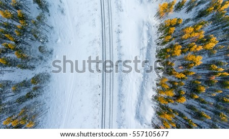 Top view at the wintry two way rail road in evergreen forest. Winter in Russia