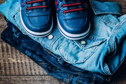 Top View. Baby clothes blue jeans, sneakers and shirt on wooden background. Stack of kids things. Copy space