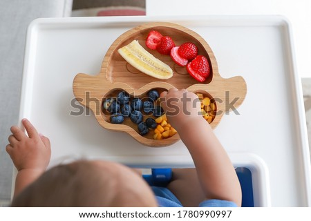 Top view Baby self-feeding with hand BLW or baby led weaning. Finger food plate of mix fruit strawberry, banana, blueberry and corn. Kid healthy nutrition eating on high chair fine motor development. Stock foto ©